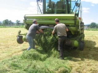 Picture of two men clearing a blockage on a harvester
